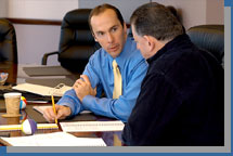At a meeting with Paul Cooperstein's Business Momentum, two clients discuss business options.