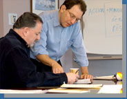 Business Momentum's Paul Cooperstein confers with a client on how to best run a company and achieve strategic goals.